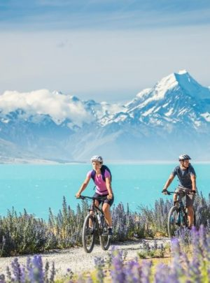 Three people cycling on Lake Pukaki with snowy mountains in background