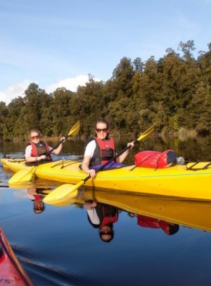 two people in yellow kayaks on lake mapourika new zealand