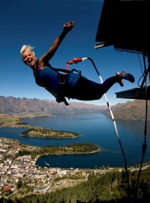 Blonde Woman Bungy Jumps with Queenstown and Lake Wakatipu backdrop