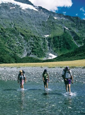 Three people hiking the Southern Lakes in Queenstown New Zealand