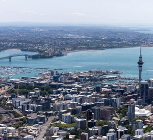 Auckland city from above with Skytower with industrial buildings below and harbour bridge against the blue harbour