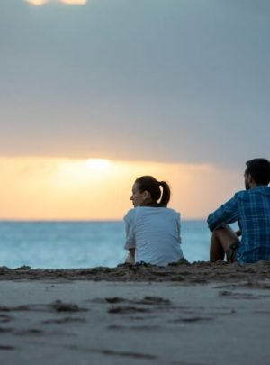Couple sitting on the beach watching sunset on Hot Water Beach Coromandel New Zealand