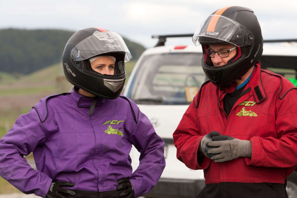 man in red and woman in purple racing clothes and helmets