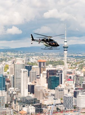 Black Helicopter flying over Auckland Skyline and Sky Tower