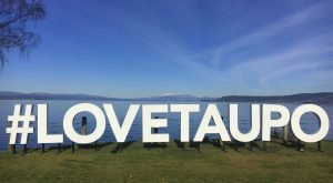 #LoveTaupo Sign on a sunny day with Lake Taupo and Tongariro National Park in the background