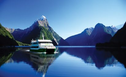 Maiden of Milford catamaran in Milford Sound New Zealand with Mitre Peak mountain and mirroring water