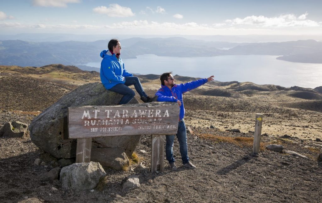 woman sitting on the summit sign on mt tarawera and man pointing at the view over the rotorua lakes