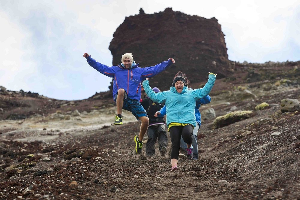 Group of people jumping and running down the scree run on the Mt Tarawera Crater Walk