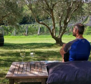 man sitting on a bean bag with a glass of wine under olive trees and looking over a vineyward on waiheke island