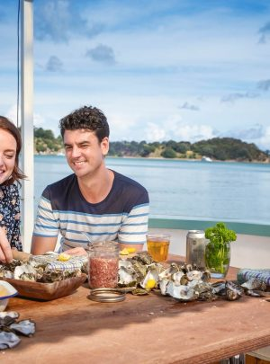 Couple eating oysters in Mahurangi, Auckland, New Zealand with the ocean in the background