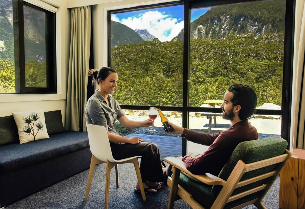 Couple drinking wine and beer with great background views in a Mountain View Chalet at Milford Sound Lodge