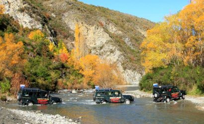 Three Land Rover Defender cars river crossing on a sunny autumn day
