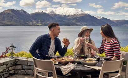 Two women and one man eating lunch at Walter Peak in Queenstown with Lake Wakatipu in the background