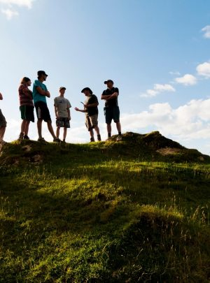 Group of people with guide standing on a hill against the sun. Guided weekend getaways