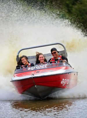 Red Agrojet jet boat with three people racing over water at Velocity Valley Rotorua