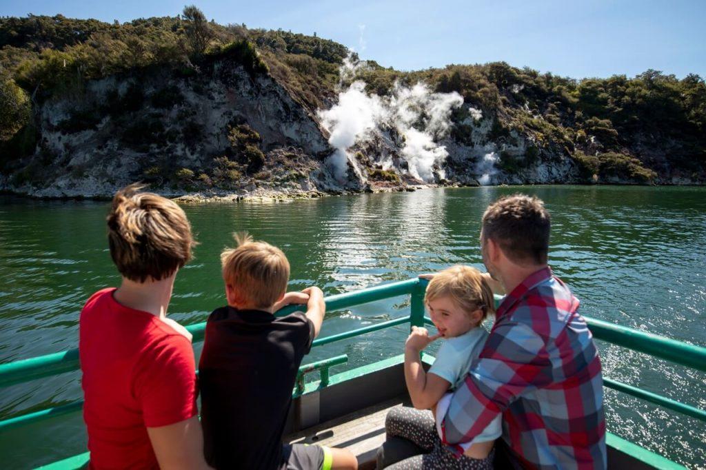 Family on boat cruising Lake Rotomahana and viewing geothermal activity at Waimangu Volcanic Valley Rotorua